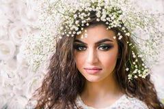 Donna attraente caucasica con i gigli sulla testa sul wa delle rose bianche Fotografia Stock Libera da Diritti