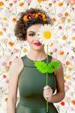 Donna attraente caucasica con una grande margherita bianca che copre un ey Fotografie Stock Libere da Diritti