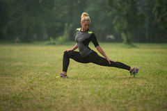 Donna attraente che allunga prima della forma fisica e dell'esercizio Immagine Stock Libera da Diritti