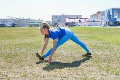 Donna attraente che allunga prima della forma fisica e dell'esercizio Immagini Stock Libere da Diritti