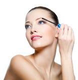Donna attraente che applica mascara sui cigli Fotografia Stock
