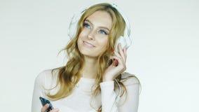 Donna attraente che ascolta la musica romantica sulle cuffie Video su un fondo bianco video d archivio