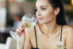 Donna attraente che assaggia vino bianco Immagini Stock