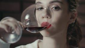 Donna attraente che beve il vino dell'uva rossa da vetro Signora che beve vino rosso video d archivio