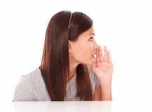 Donna attraente che bisbiglia e che guarda a sinistra Fotografie Stock Libere da Diritti