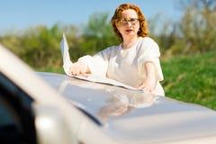 Donna attraente che controlla posizione in mappa di carta sul cofano fotografie stock