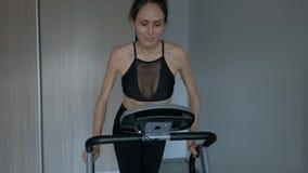 Donna attraente che corre a casa su una pedana mobile archivi video