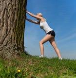 Donna attraente che fa allungando esercitazione all'esterno Fotografie Stock