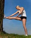 Donna attraente che fa allungando esercitazione all'esterno Immagine Stock
