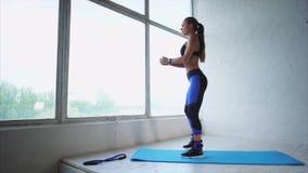Donna attraente che fa gli esercizi sui muscoli delle natiche in società polisportiva video d archivio