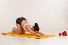 Donna attraente che fa le esercitazioni Ente castana di misura sulla stuoia di yoga immagine stock