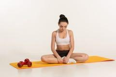 Donna attraente che fa le esercitazioni Ente castana di misura sulla stuoia di yoga Immagini Stock Libere da Diritti