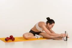 Donna attraente che fa le esercitazioni Ente castana di misura sulla stuoia di yoga Immagini Stock