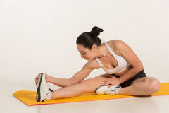 Donna attraente che fa le esercitazioni Ente castana di misura sulla stuoia di yoga Fotografia Stock