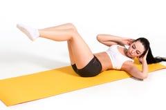 Donna attraente che fa le esercitazioni Ente castana di misura sulla stuoia di yoga Fotografie Stock