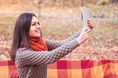 Donna attraente che fa selfie in un parco Fotografia Stock