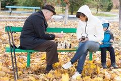Donna attraente che gioca scacchi con suo padre Immagine Stock