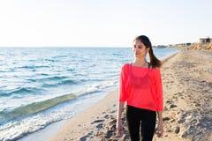 Donna attraente che gode del giorno soleggiato dopo addestramento di allenamento alla spiaggia di estate Fotografie Stock Libere da Diritti
