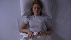 Donna attraente che grida menzogne nel suo letto alla notte, alla debolezza femminile ed alla fragilità stock footage