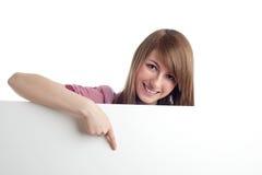 Donna attraente che indica segno in bianco. Sorridere. Immagini Stock Libere da Diritti