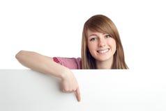 Donna attraente che indica segno in bianco. Sorridere. Immagini Stock