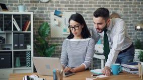 Donna attraente che lavora con il computer portatile poi che discute lavoro con il collega maschio video d archivio