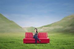 Donna attraente che mangia caffè sul sofà rosso all'aperto Fotografia Stock Libera da Diritti