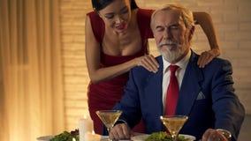 Donna attraente che massaggia le spalle dell'uomo anziano, prossimità delle coppie, affetto immagine stock