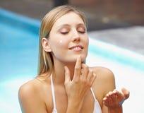 Donna attraente che mette protezione solare sul fronte Fotografia Stock