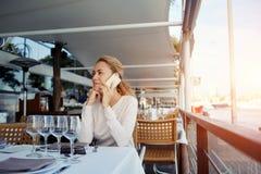 Donna attraente che parla sul telefono cellulare mentre aspettando qualcuno per pranzo in ristorante accogliente moderno, Immagini Stock