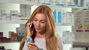 Donna attraente che parla sul telefono, comperante alla farmacia archivi video