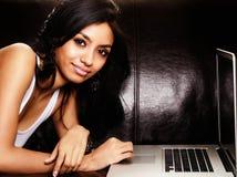 Donna attraente che per mezzo del computer portatile Fotografie Stock