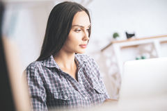 Donna attraente che per mezzo del computer portatile Immagine Stock