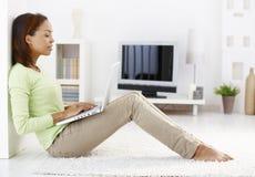 Donna attraente che per mezzo del computer portatile sul pavimento Immagini Stock Libere da Diritti