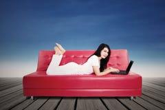 Donna attraente che per mezzo del computer portatile sul sofà Fotografia Stock