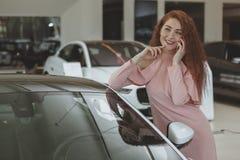 Donna attraente che per mezzo del suo Smart Phone mentre bying nuova automobile fotografie stock
