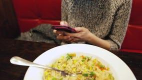 Donna attraente che per mezzo dello smartphone e mangiando in un caffè archivi video