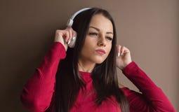 Donna attraente che porta maglione rosso in cuffie Immagini Stock