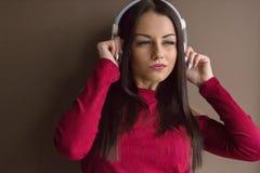 Donna attraente che porta maglione rosso in cuffie Fotografia Stock