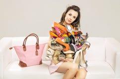 Donna attraente che porta un mucchio delle scarpe immagine stock