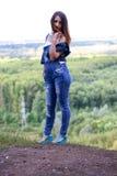 Donna attraente che posa contro il contesto della foresta Fotografia Stock Libera da Diritti
