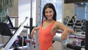 Donna attraente che posa il simulatore sexy stretto del vestito di sport in palestra video d archivio