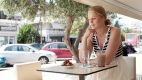 Donna attraente che prende immagine di una pasticceria sul suo cellulare video d archivio