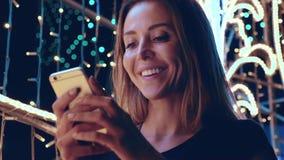 Donna attraente che ride con un telefono in sue mani durante il nuovo anno archivi video