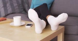 Donna attraente che riposa i suoi piedi sulla tavola Fotografie Stock Libere da Diritti
