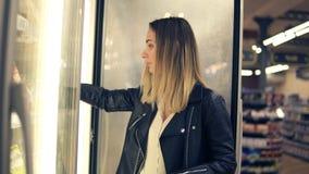 Donna attraente che sceglie i prodotti lattier-caseario nel supermercato in frigorifero Prodotti congelati prese della giovane do archivi video