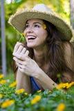 Donna attraente che sente l'odore di un fiore Fotografie Stock Libere da Diritti
