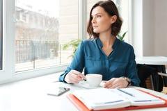 Donna attraente che si siede alla tavola del caffè ed al caffè bevente Fotografia Stock