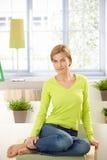 Donna attraente che si siede nel paese nel verde chiaro Immagine Stock