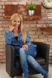 Donna attraente che si siede in poltrona Immagine Stock
